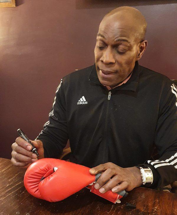 Frank Bruno signing a glove